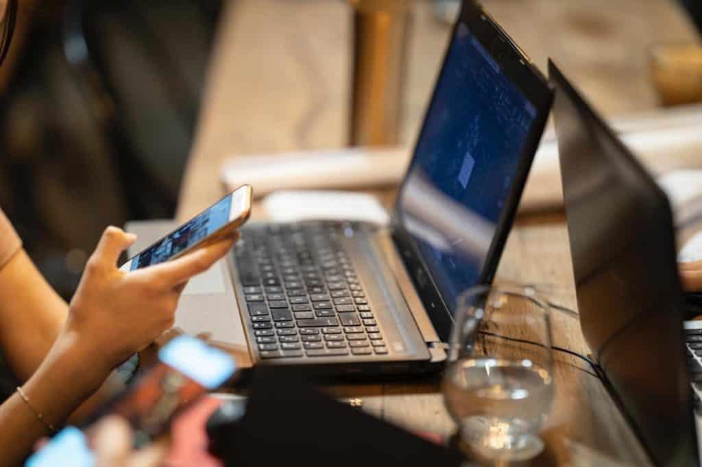 Mulher mexendo no celular e com notebook aberto na wi-fi 6